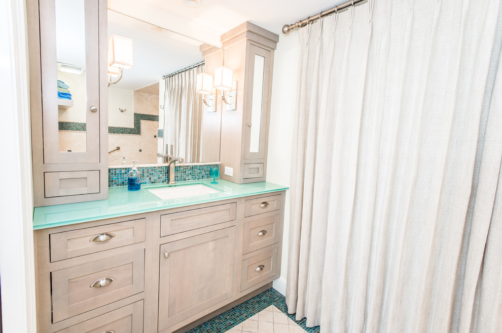Large beach style master blue tile and mosaic tile mosaic tile floor bathroom photo in Miami with shaker cabinets, light wood cabinets, a two-piece toilet, beige walls, an undermount sink and glass countertops