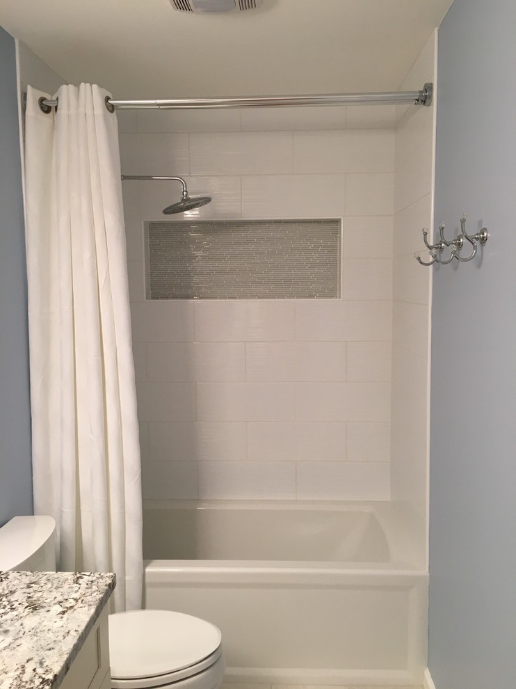 Example of a mid-sized transitional kids' white tile and porcelain tile ceramic tile and beige floor bathroom design in New York with a two-piece toilet, blue walls, shaker cabinets, white cabinets and an undermount sink