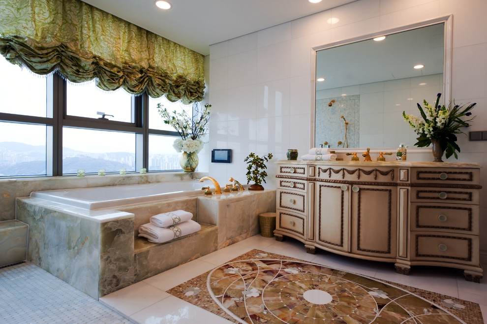 Elegant white tile drop-in bathtub photo in New York with furniture-like cabinets and beige cabinets