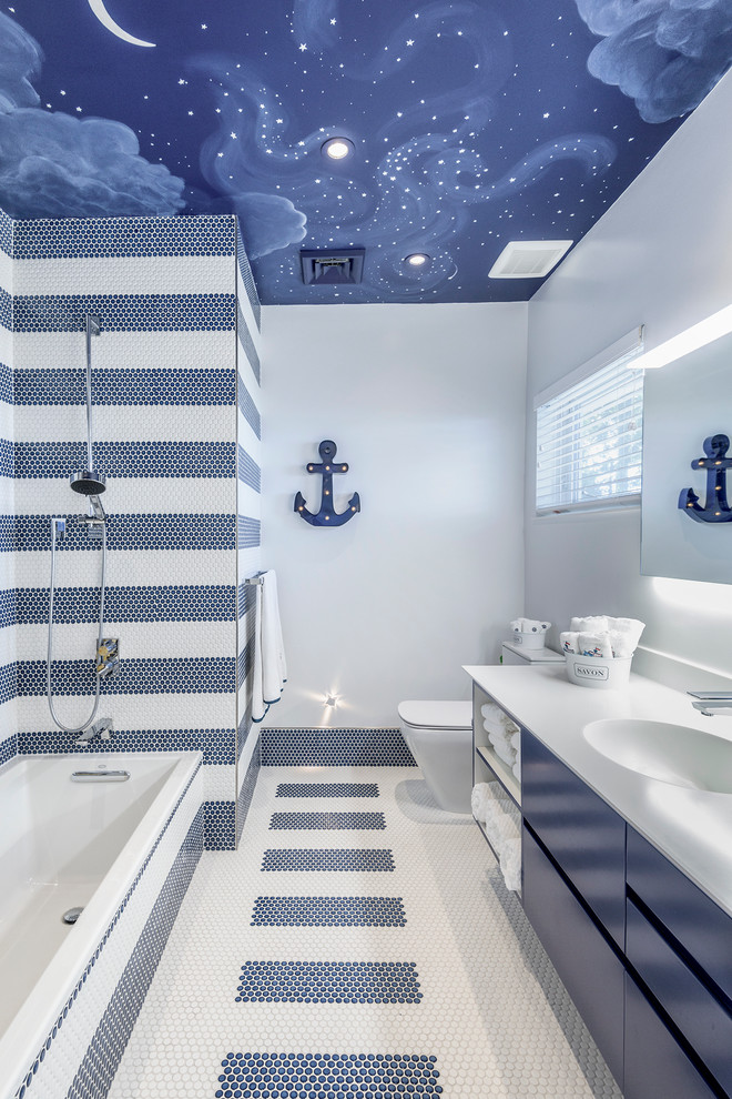 Small trendy kids' multicolored tile and mosaic tile mosaic tile floor bathroom photo in Miami with flat-panel cabinets, blue cabinets, a one-piece toilet, multicolored walls, an integrated sink and solid surface countertops