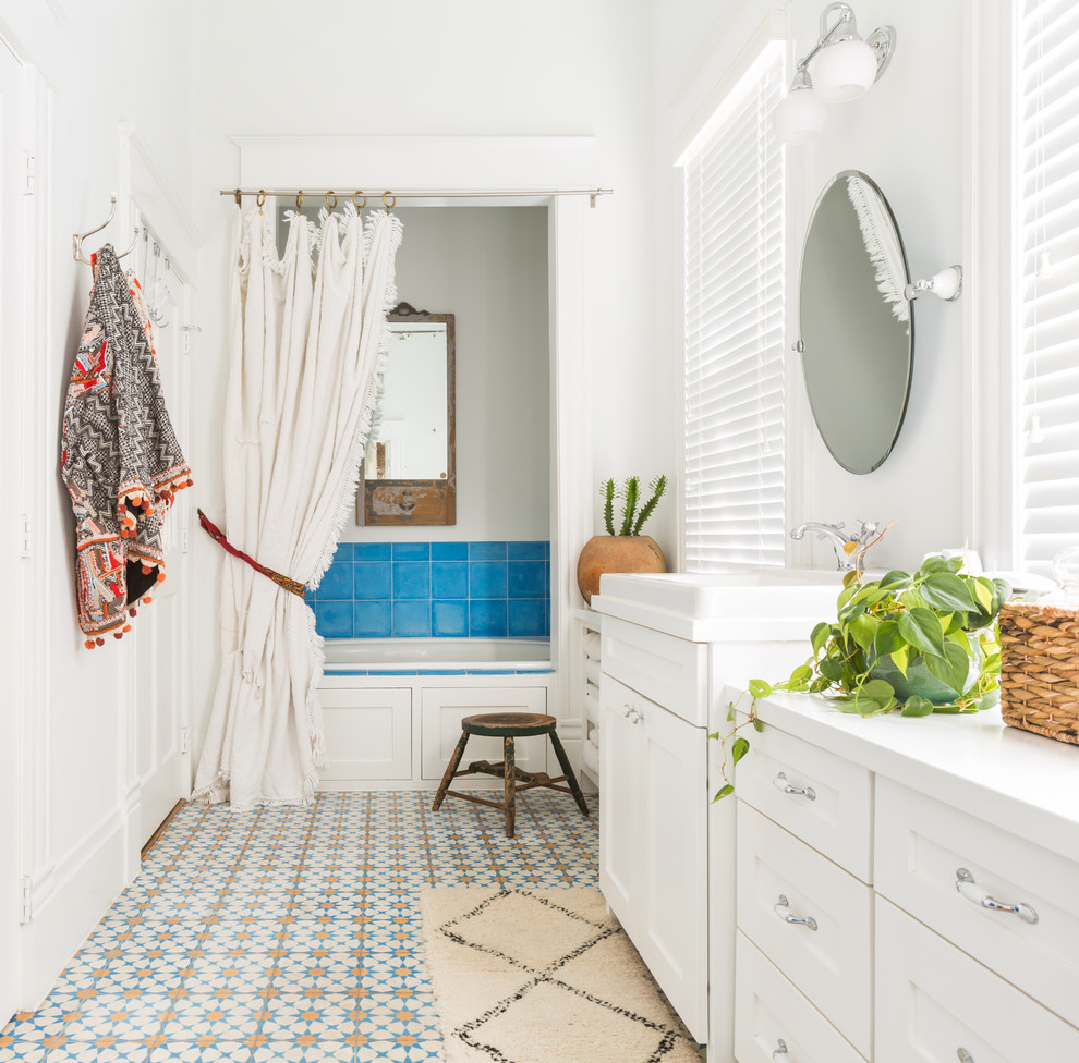 Example of a mid-sized tuscan master blue tile, multicolored tile and ceramic tile multicolored floor and ceramic tile bathroom design in Houston with shaker cabinets, white cabinets, white walls, a drop-in sink and a hinged shower door
