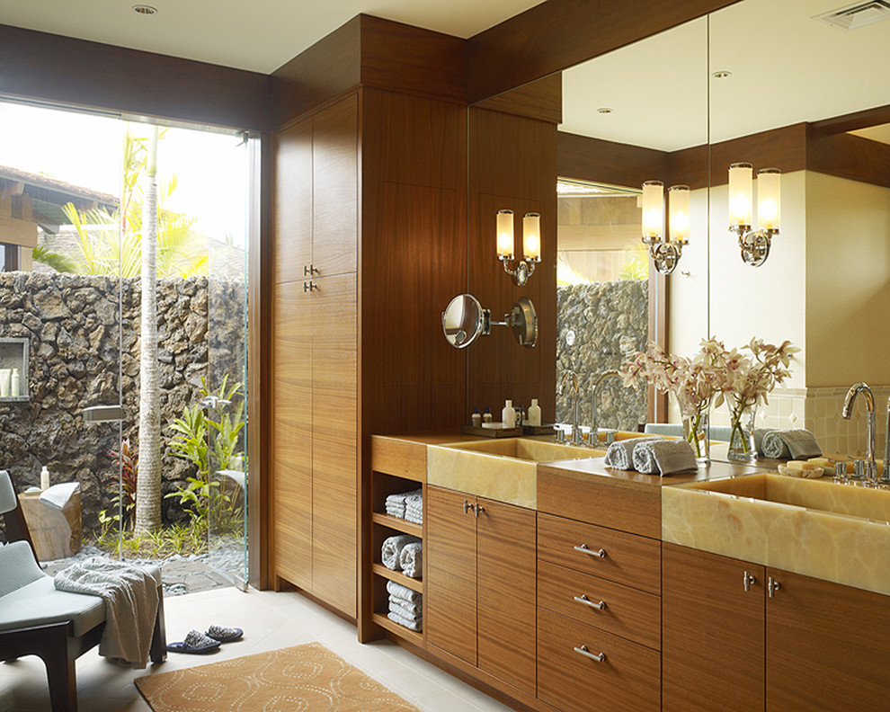 Example of an island style bathroom design in Hawaii with flat-panel cabinets and medium tone wood cabinets
