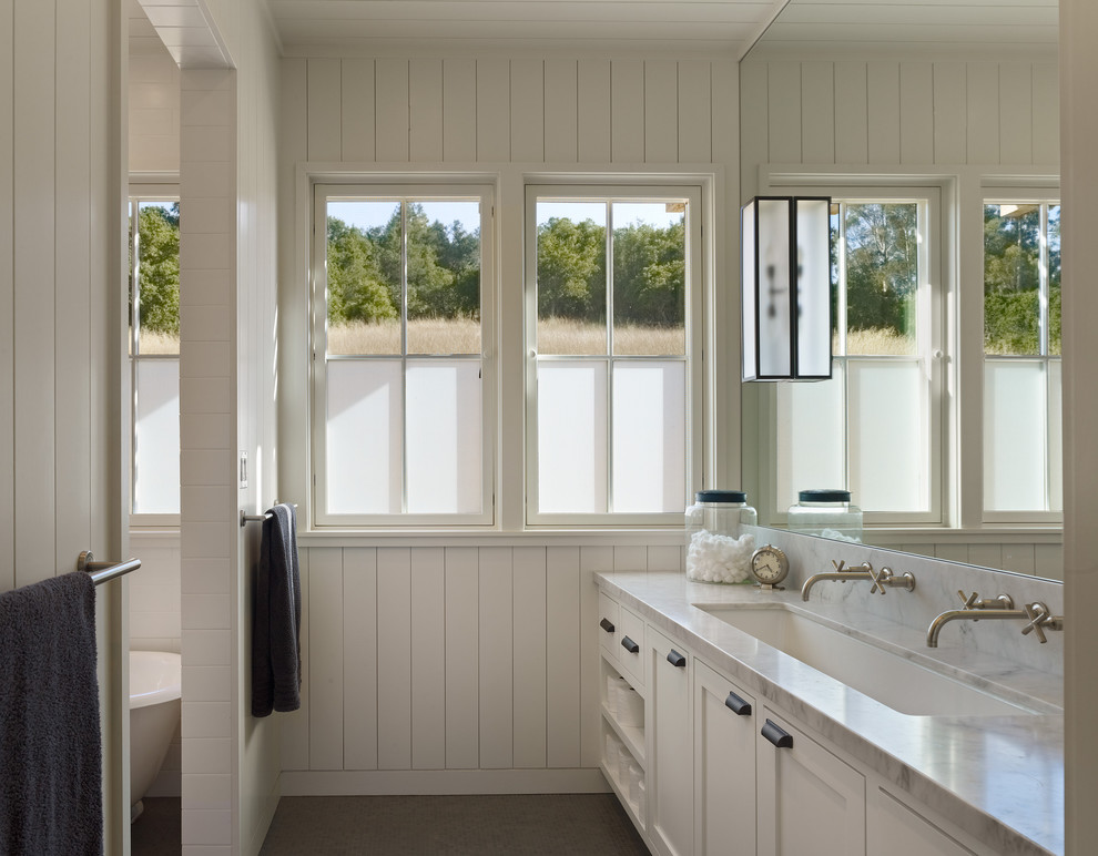 Example of a farmhouse bathroom design in San Francisco with marble countertops and a trough sink