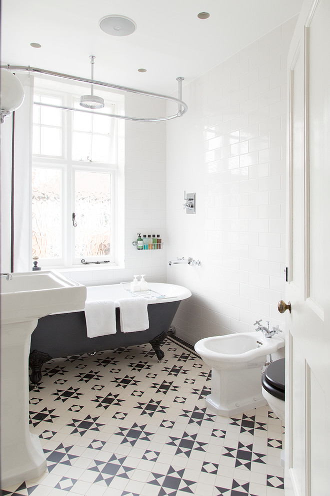 Mid-sized elegant white tile and subway tile ceramic tile bathroom photo in London with a bidet, white walls and a pedestal sink