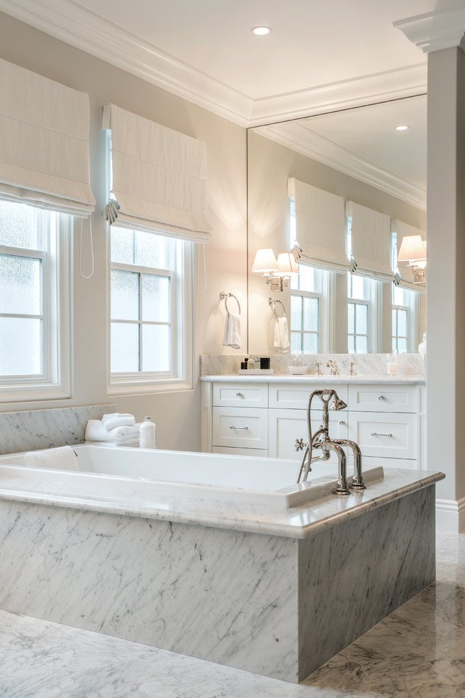 Drop-in bathtub - large transitional master white tile and stone tile marble floor drop-in bathtub idea in Orange County with shaker cabinets, white cabinets, an undermount sink, marble countertops, beige walls and white countertops