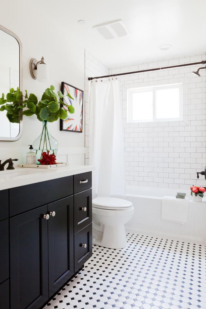 Inspiration for a beach style white tile and subway tile mosaic tile floor and multicolored floor bathroom remodel in Los Angeles with an undermount sink, black cabinets, a two-piece toilet and recessed-panel cabinets