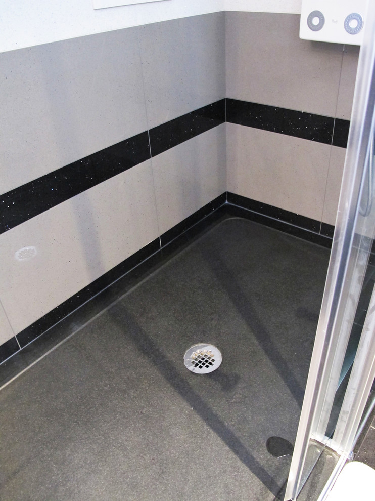 Example of a huge trendy master black tile and stone tile porcelain tile bathroom design in Montreal with an undermount sink, raised-panel cabinets, medium tone wood cabinets, quartz countertops, a one-piece toilet and gray walls