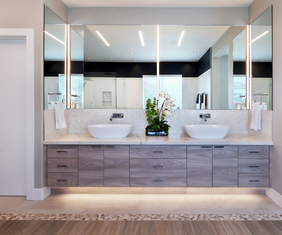 Example of a beach style porcelain tile bathroom design in Orange County with flat-panel cabinets, gray cabinets and a vessel sink