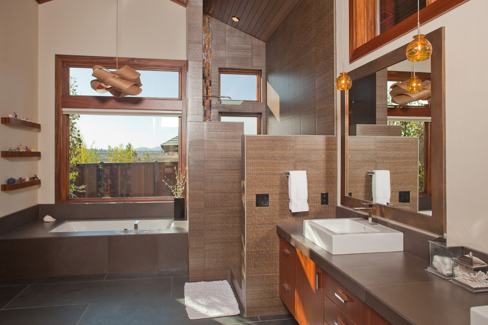Large trendy master porcelain tile and brown tile slate floor and gray floor corner shower photo in Portland with flat-panel cabinets, medium tone wood cabinets, an undermount tub, a two-piece toilet, beige walls, a vessel sink, solid surface countertops, a hinged shower door and gray countertops