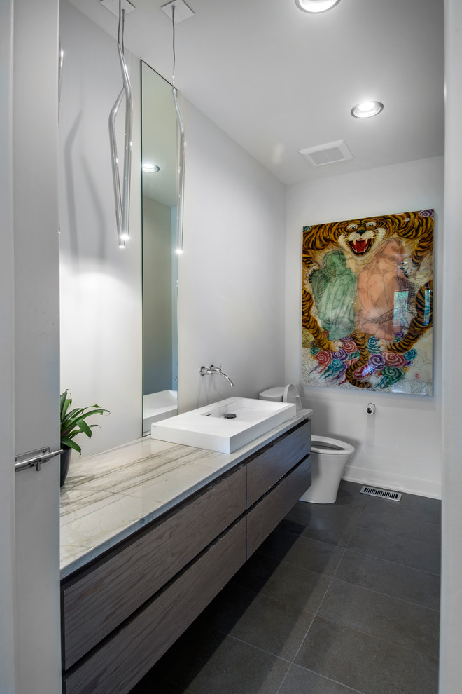 Mid-sized trendy 3/4 gray tile and porcelain tile porcelain tile and gray floor bathroom photo in Other with a vessel sink, flat-panel cabinets, white walls, gray cabinets, a one-piece toilet and quartzite countertops