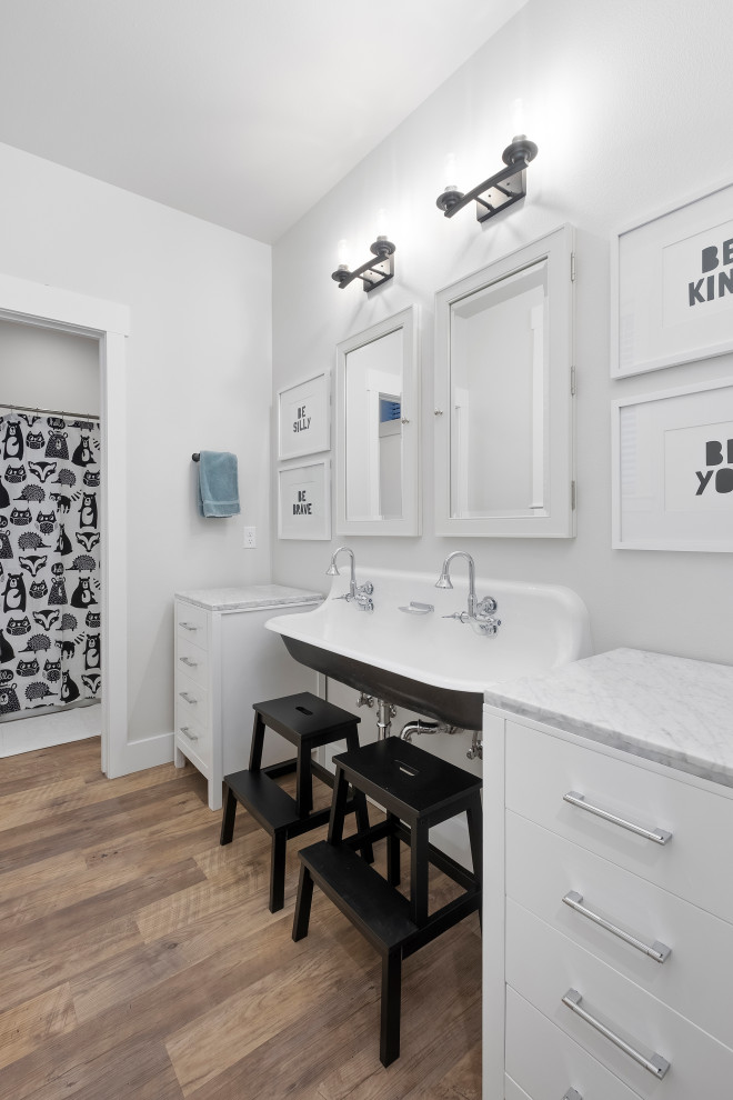 Example of a transitional kids' brown floor and double-sink bathroom design in Other with flat-panel cabinets, white cabinets, gray walls, a trough sink, gray countertops and a freestanding vanity