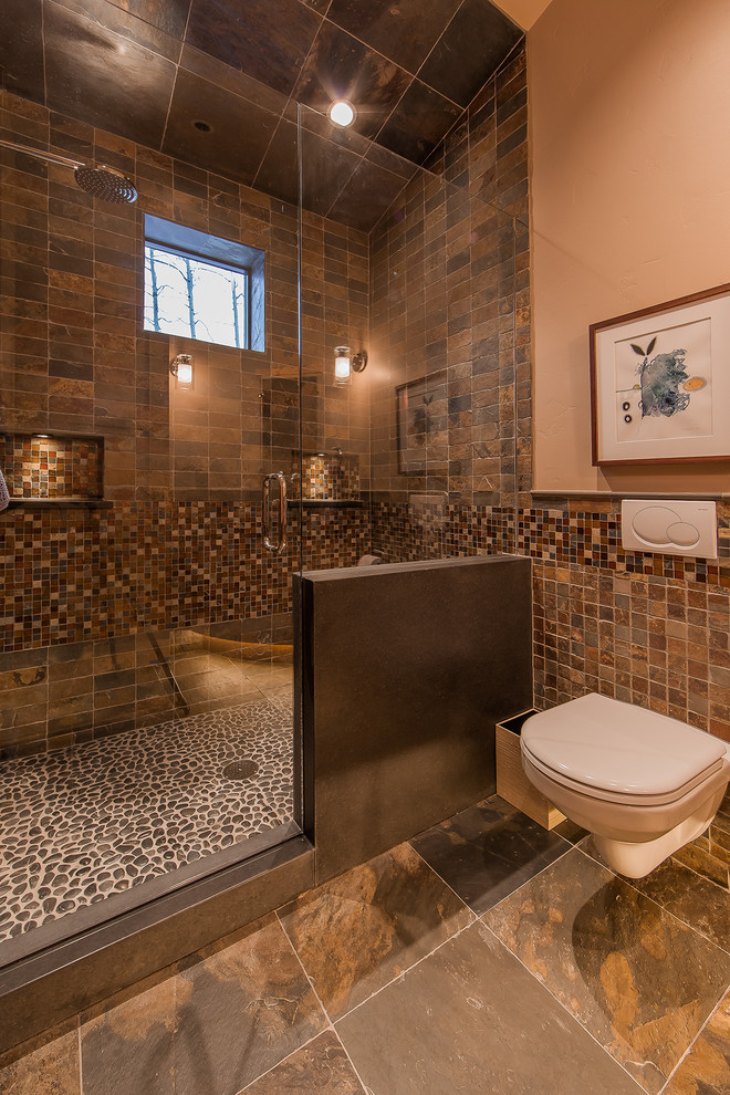 Mountain style brown tile brown floor alcove shower photo in Denver with a wall-mount toilet