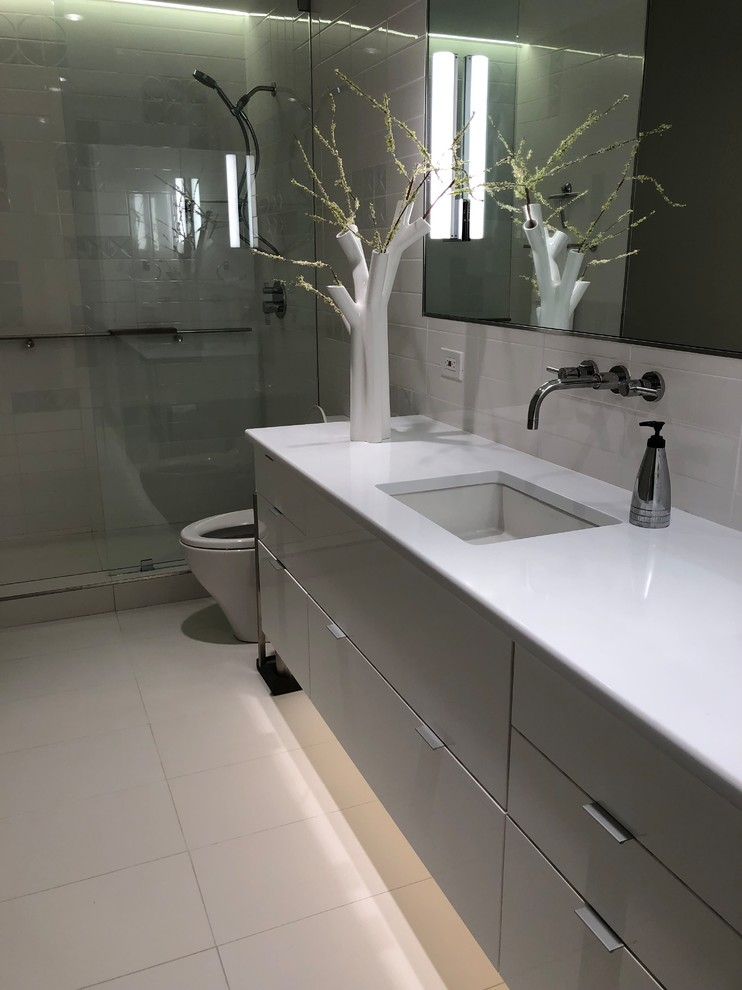 Example of a small minimalist master white tile and ceramic tile porcelain tile and white floor bathroom design in Dallas with glass-front cabinets, gray cabinets, a one-piece toilet, gray walls, an undermount sink, quartz countertops and white countertops