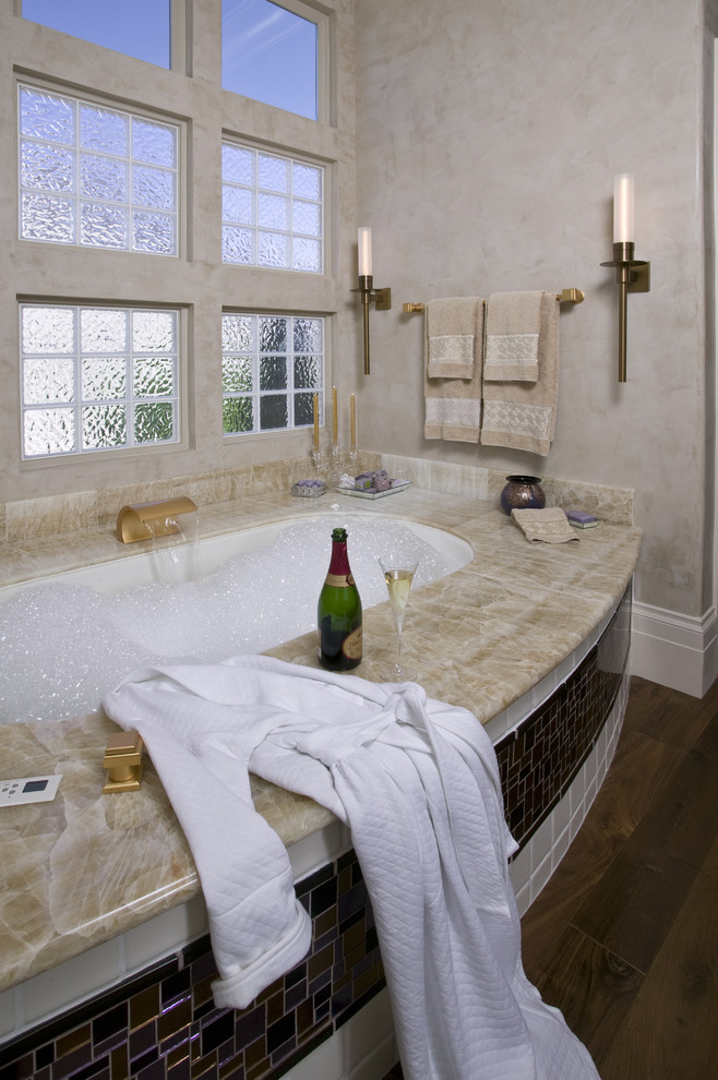 Inspiration for a mid-sized contemporary master glass tile and beige tile dark wood floor and brown floor corner shower remodel in Sacramento with an undermount sink, flat-panel cabinets, an undermount tub, beige walls, purple cabinets, a one-piece toilet, onyx countertops, a hinged shower door and beige countertops