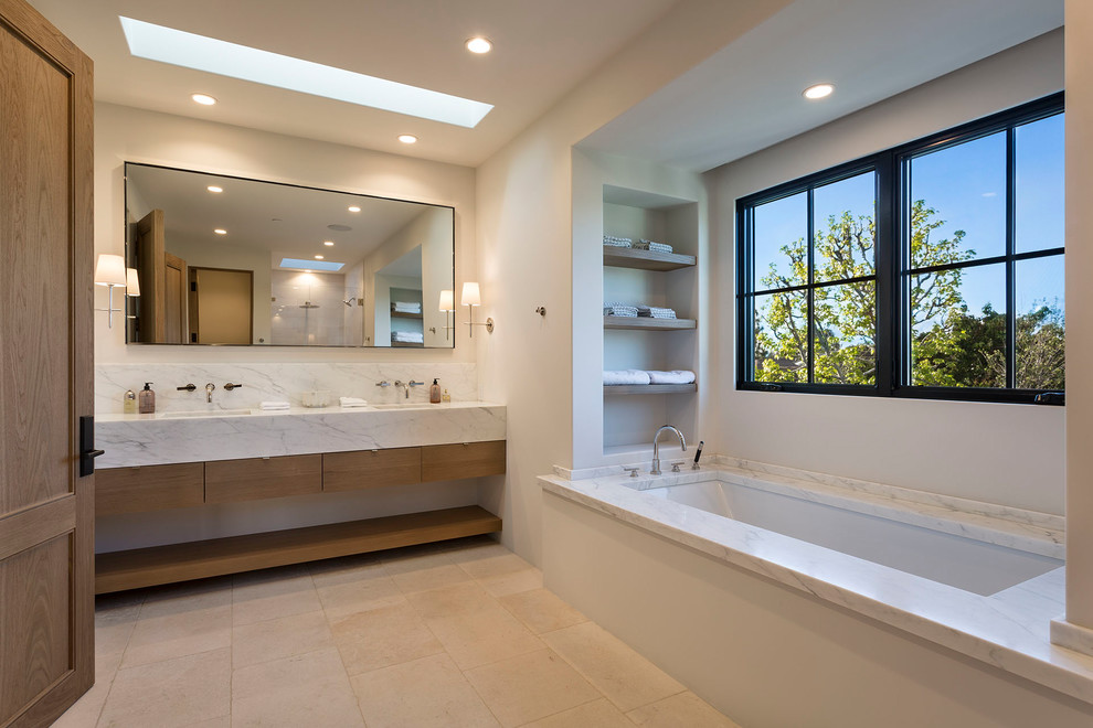 Trendy master beige floor bathroom photo in Boise with flat-panel cabinets, medium tone wood cabinets, an undermount tub and white walls