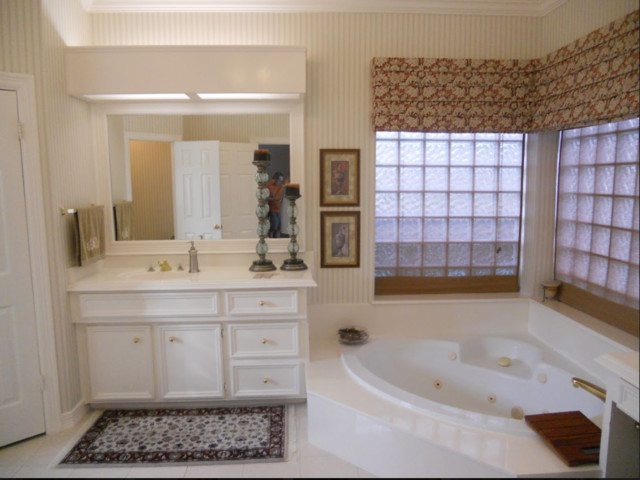 Corner bathtub - mid-sized traditional master porcelain floor and white floor corner bathtub idea in Houston with recessed-panel cabinets, white cabinets, beige walls, an integrated sink, solid surface countertops and white countertops