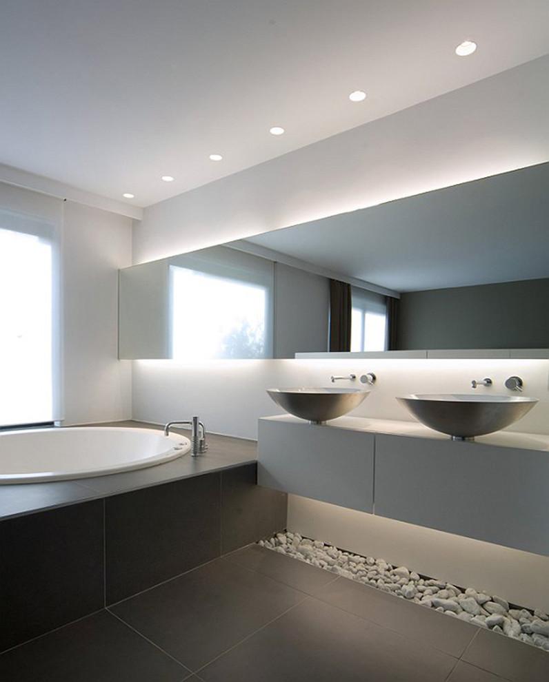 Imagen de cuarto de baño principal, contemporáneo, grande, con armarios con paneles lisos, puertas de armario blancas, suelo de baldosas de cerámica, paredes grises, lavabo sobreencimera, baldosas y/o azulejos grises y bañera encastrada