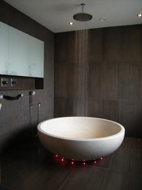 baño con ducha y bañera redonda en el mismo lugar