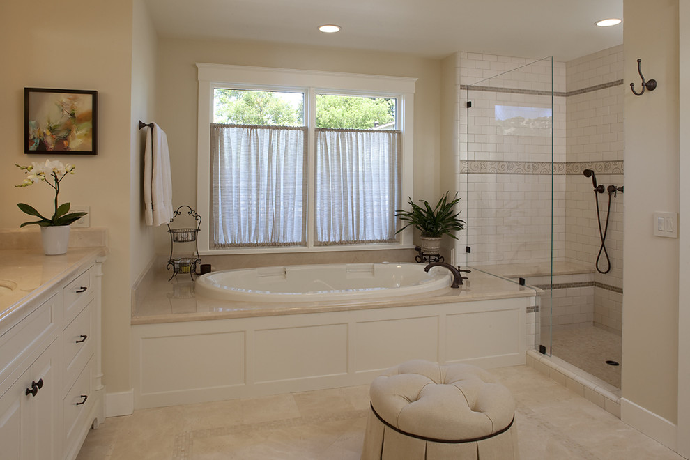 Elegant white tile and subway tile bathroom photo in San Francisco with an undermount sink, raised-panel cabinets, white cabinets and beige countertops