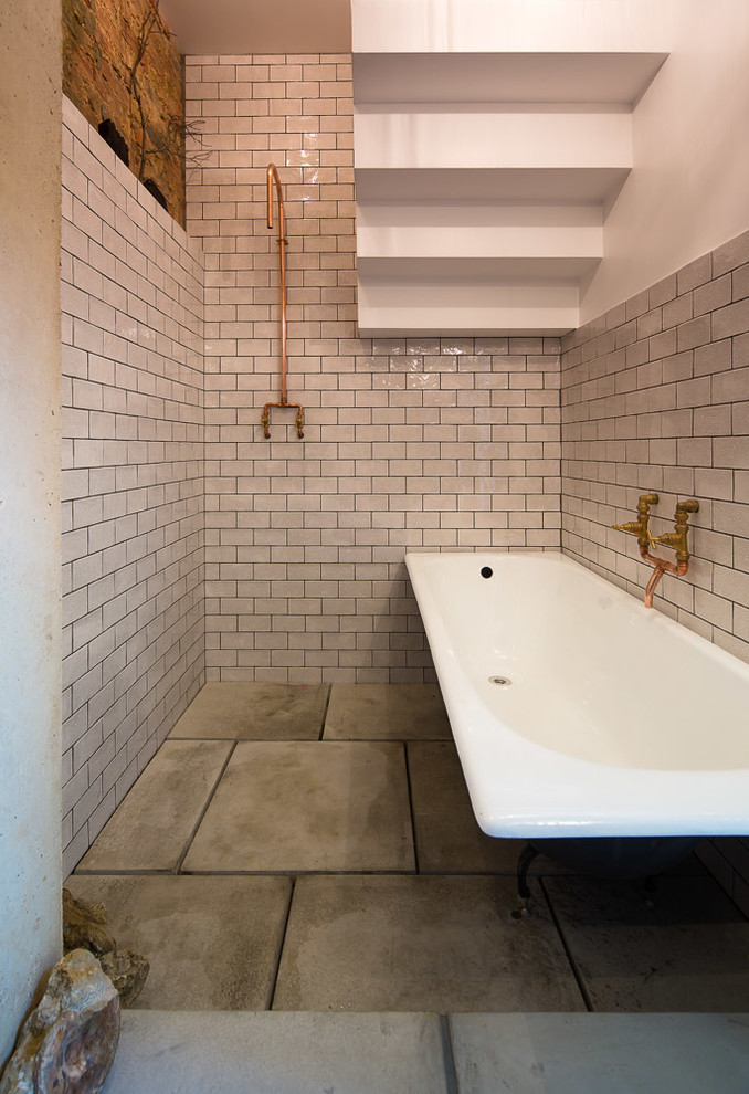 Urban white tile and ceramic tile concrete floor bathroom photo in London with white walls