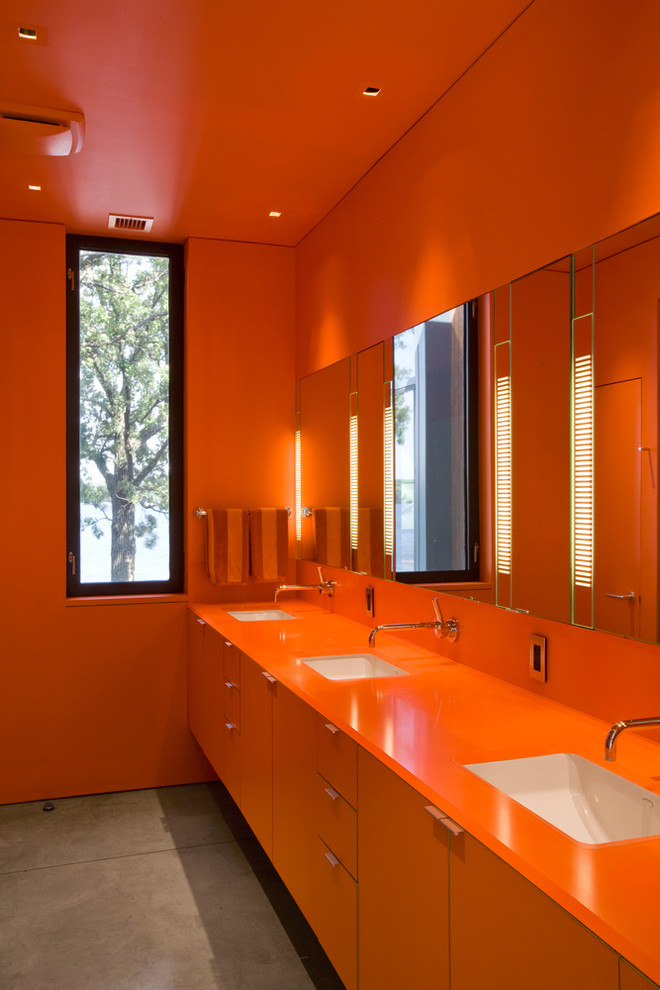Inspiration for a modern bathroom remodel in Omaha with an undermount sink, flat-panel cabinets, orange cabinets, orange walls and orange countertops