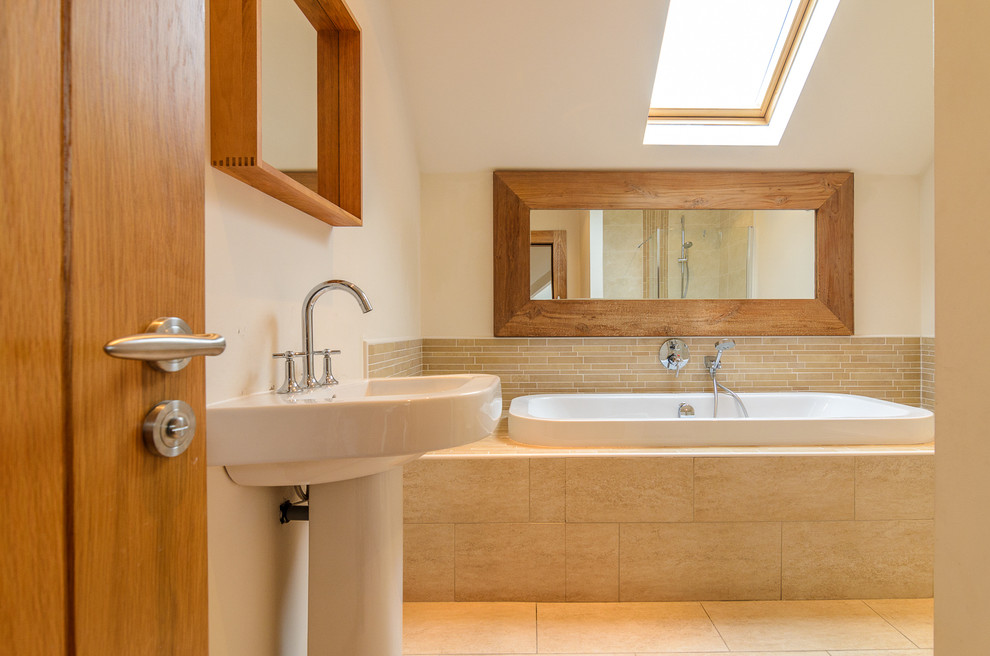 Example of a classic beige tile and matchstick tile travertine floor drop-in bathtub design in Belfast with a pedestal sink and beige walls