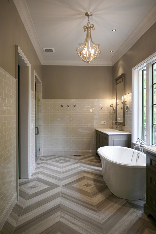 Example of a large trendy master gray tile and stone tile limestone floor freestanding bathtub design in Atlanta with beige walls, recessed-panel cabinets, gray cabinets, an undermount sink and marble countertops
