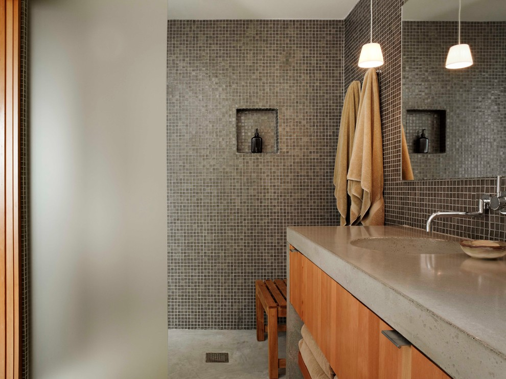 Inspiration for a modern brown tile and mosaic tile concrete floor bathroom remodel in San Francisco with an integrated sink, flat-panel cabinets, medium tone wood cabinets and concrete countertops