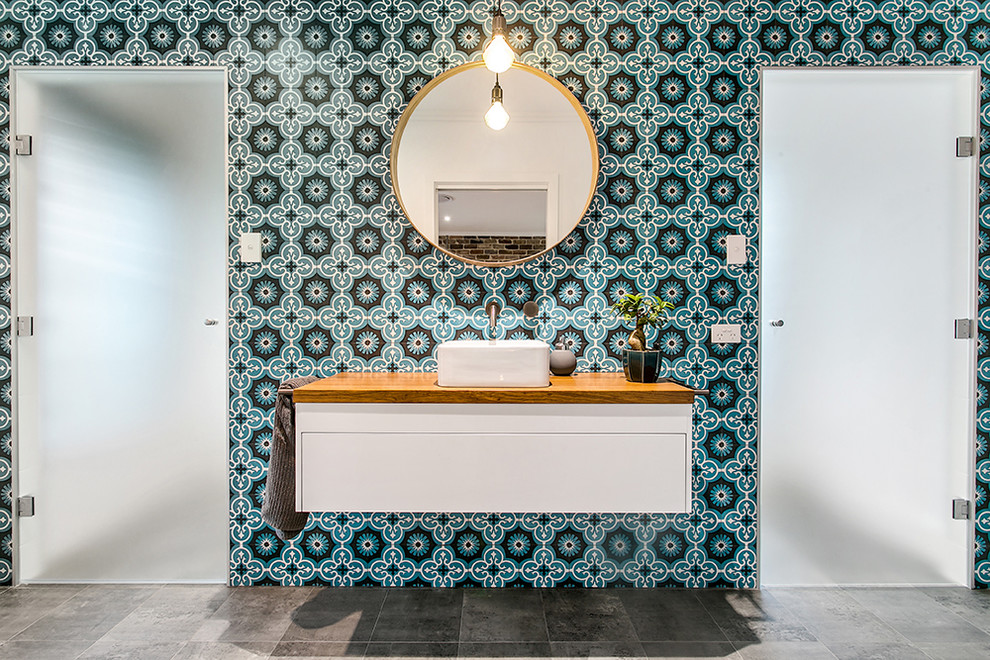 Inspiration for a contemporary multicolored tile and cement tile gray floor bathroom remodel in Other with flat-panel cabinets, white cabinets, a vessel sink, wood countertops, a hinged shower door and brown countertops