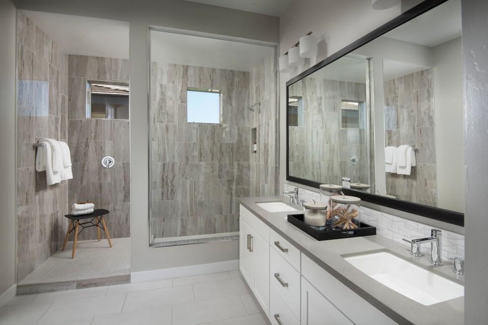Modelo de cuarto de baño principal, contemporáneo, con armarios estilo shaker, puertas de armario blancas, ducha esquinera, baldosas y/o azulejos grises, baldosas y/o azulejos de porcelana, paredes grises, suelo de baldosas de porcelana, lavabo bajoencimera, encimera de cuarzo compacto, suelo blanco, ducha abierta y encimeras grises