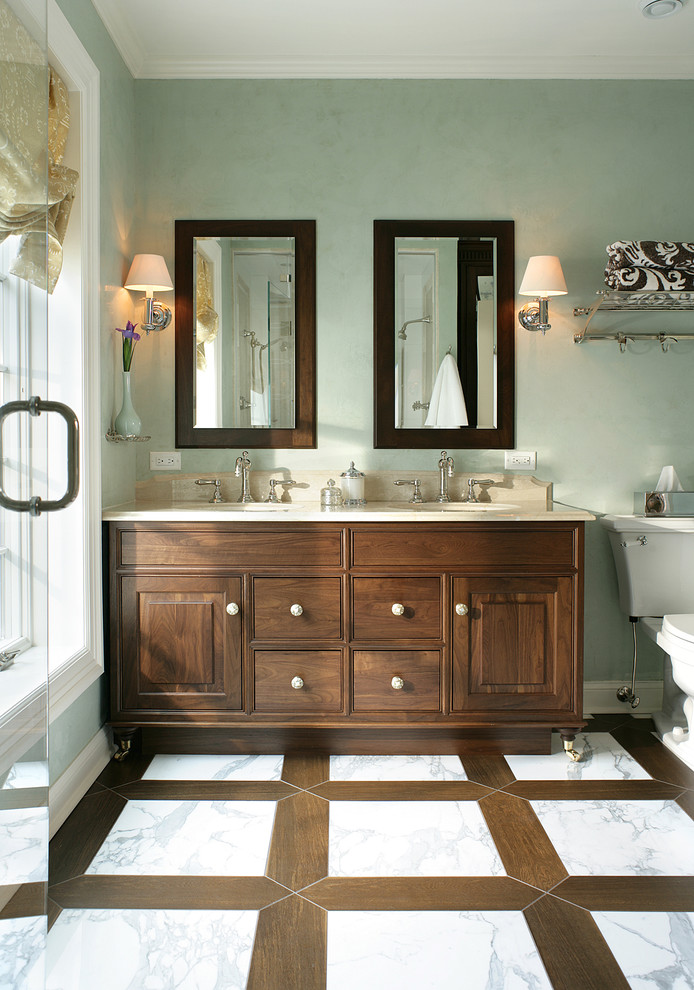 Mid-sized elegant master white tile and stone tile marble floor and white floor alcove shower photo in New York with dark wood cabinets, a two-piece toilet, green walls, an undermount sink, limestone countertops, raised-panel cabinets and a hinged shower door