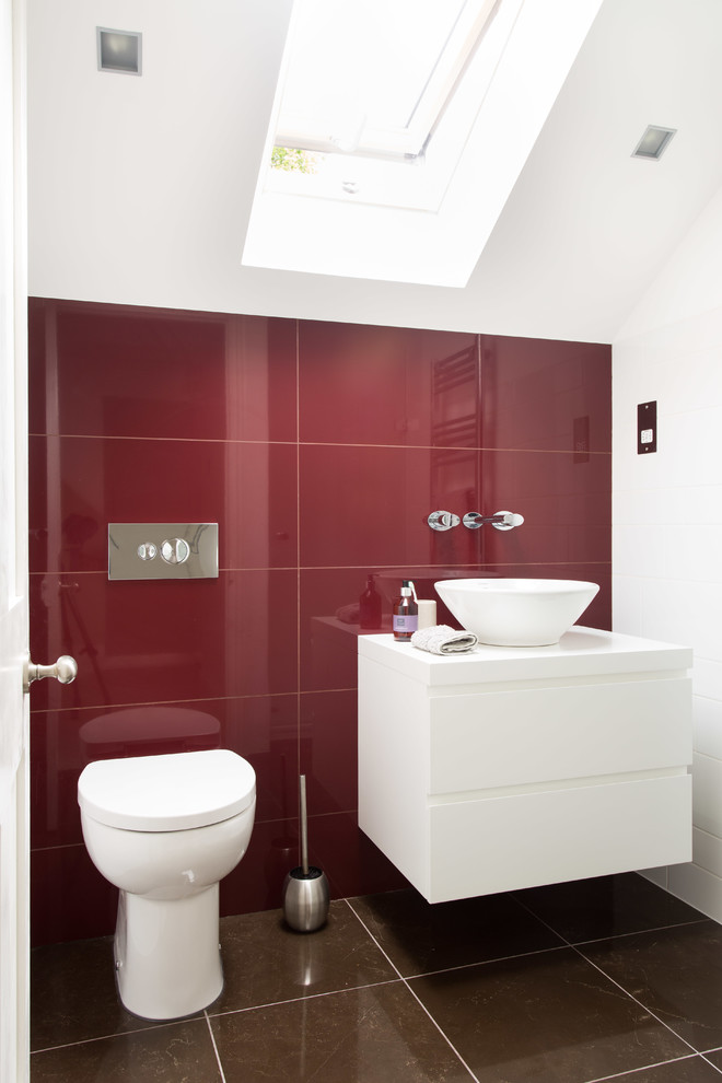 Example of a small trendy red tile and ceramic tile ceramic tile and brown floor bathroom design in Other with a vessel sink, a one-piece toilet, flat-panel cabinets, white cabinets, red walls and white countertops