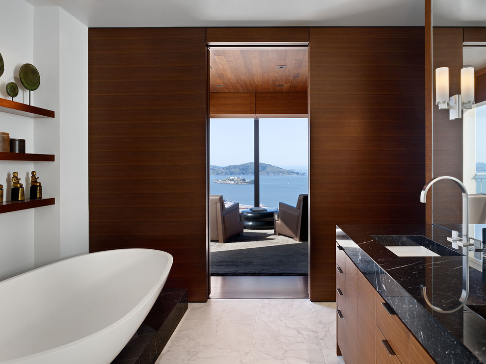 Example of a minimalist freestanding bathtub design in San Francisco with flat-panel cabinets and medium tone wood cabinets