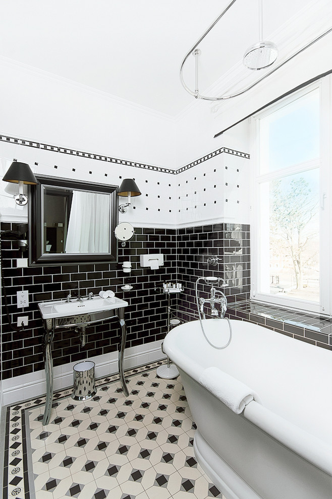Freestanding bathtub - traditional subway tile and black and white tile freestanding bathtub idea in Other with a console sink