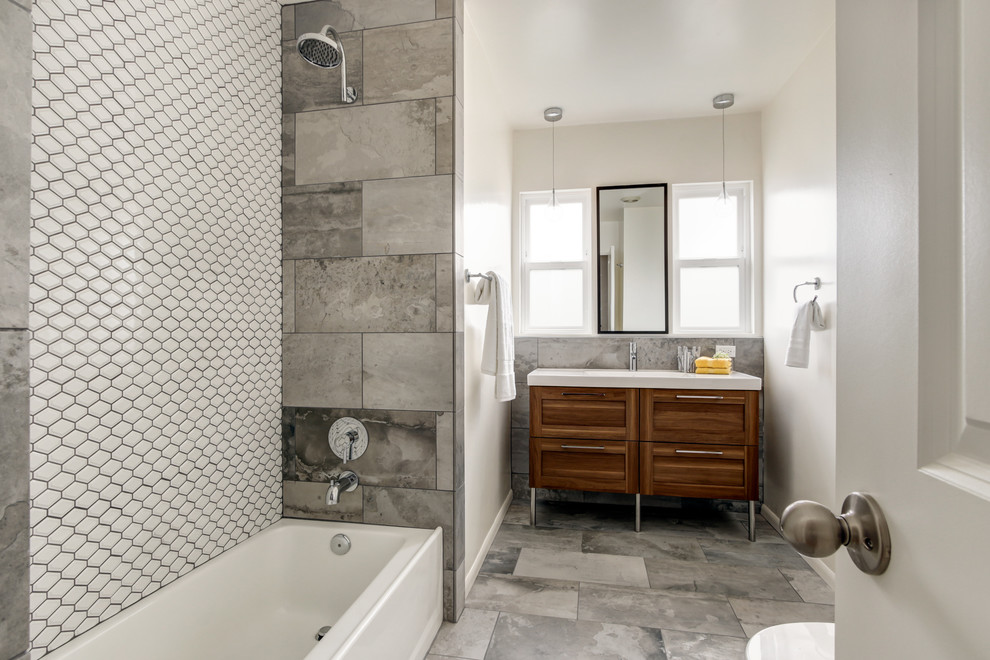 Bathroom - mid-sized contemporary gray tile and porcelain tile porcelain tile bathroom idea in San Diego with furniture-like cabinets, medium tone wood cabinets, a one-piece toilet, white walls, an integrated sink and solid surface countertops