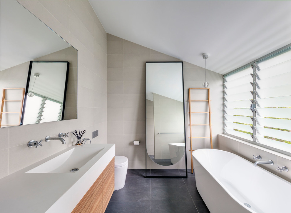 Inspiration for a contemporary master bathroom in Newcastle - Maitland with flat-panel cabinets, medium wood cabinets, a freestanding tub, a curbless shower, a one-piece toilet, beige tile, beige walls, an integrated sink and grey floor.