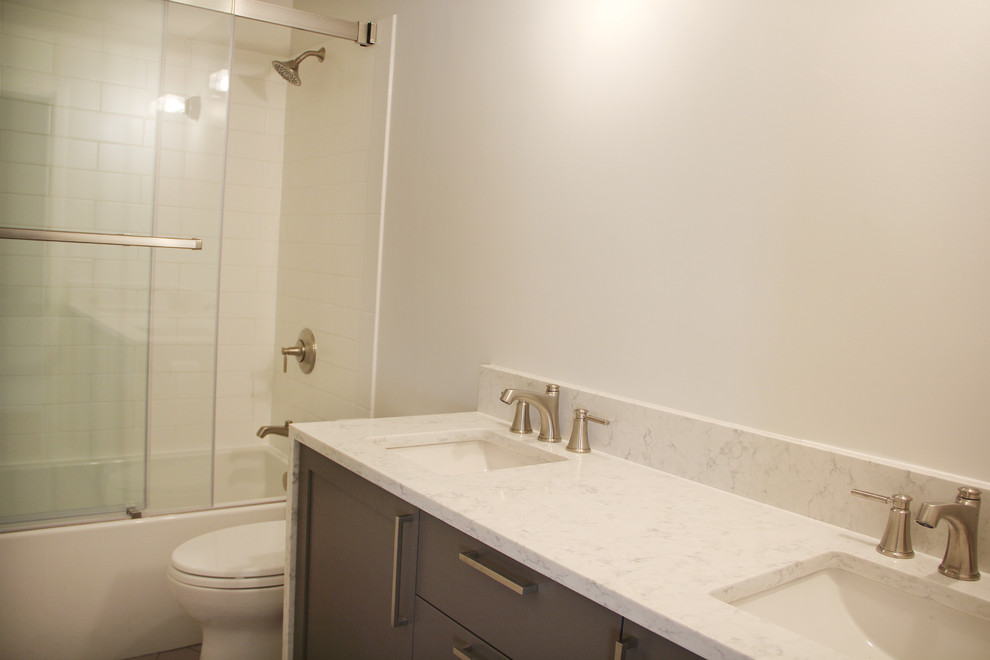 Mid-sized minimalist 3/4 white tile and subway tile bathroom photo in Portland with shaker cabinets, gray cabinets, white walls, an undermount sink and quartz countertops