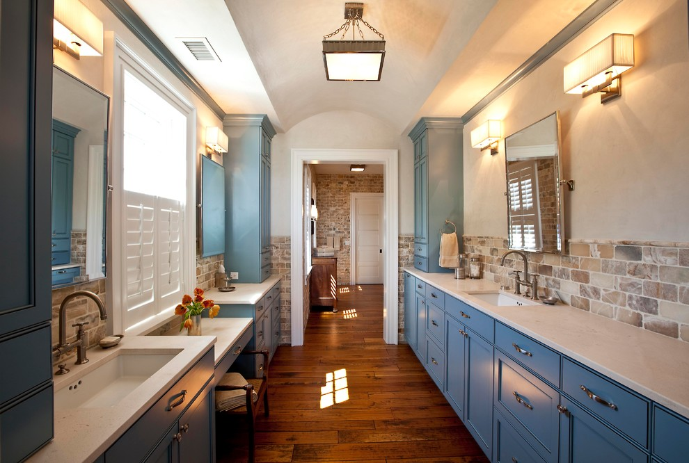 Bathroom - transitional beige tile and stone tile bathroom idea in Charleston with an undermount sink, recessed-panel cabinets, blue cabinets and white countertops