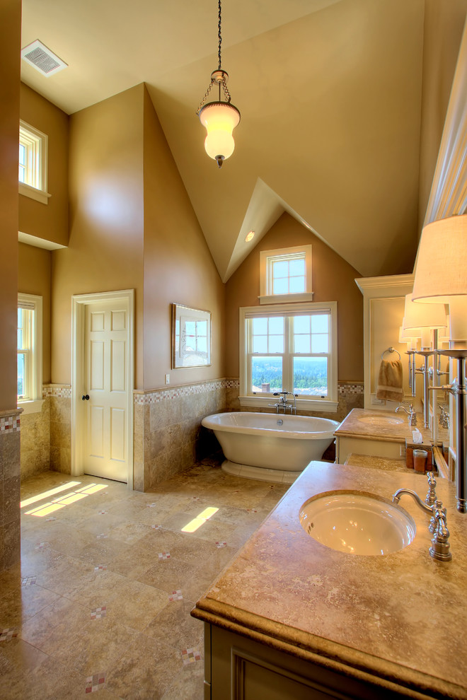 Example of a classic travertine tile freestanding bathtub design in Seattle