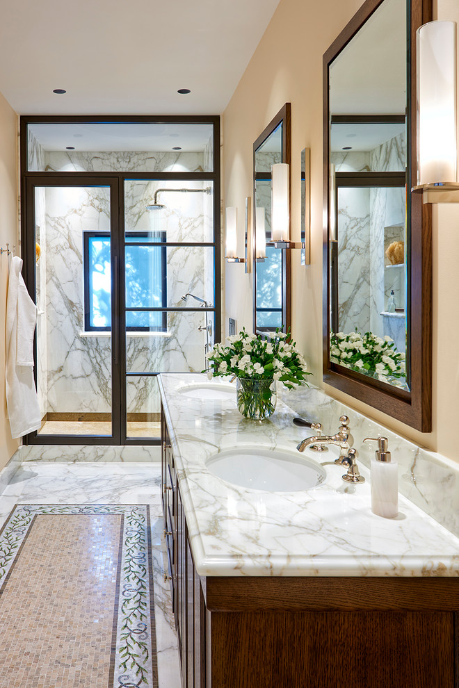 Inspiration for a large mediterranean master white tile and marble tile marble floor and white floor alcove shower remodel in San Francisco with medium tone wood cabinets, beige walls, an undermount sink, marble countertops, a hinged shower door, white countertops and raised-panel cabinets