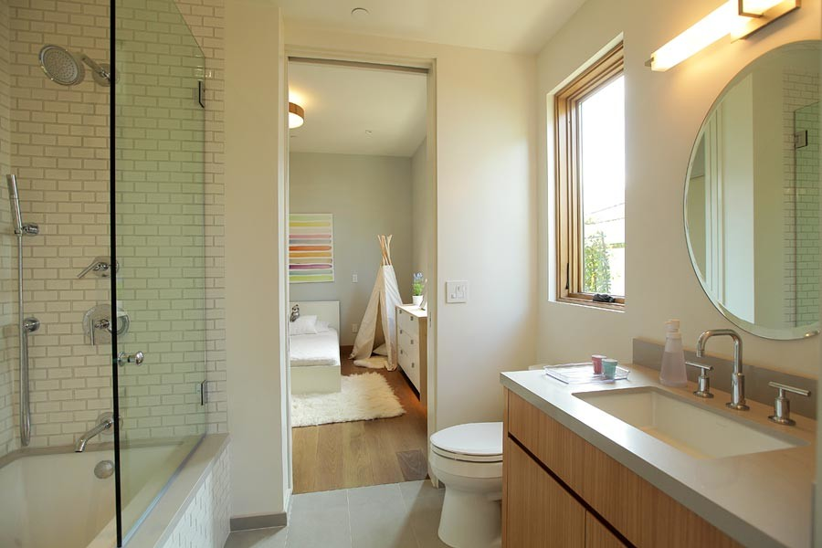 Example of a mid-sized 1950s kids' white tile and porcelain tile medium tone wood floor bathroom design in Los Angeles with an undermount sink, flat-panel cabinets, medium tone wood cabinets, quartz countertops, a one-piece toilet and white walls