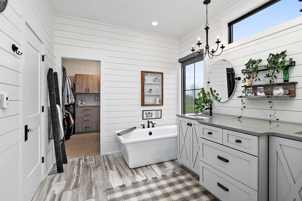 Freestanding bathtub - country master gray floor freestanding bathtub idea in Grand Rapids with shaker cabinets, gray cabinets, white walls, an undermount sink, quartz countertops and gray countertops