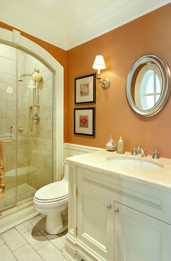 Inspiration for a mid-sized timeless 3/4 stone tile porcelain tile alcove shower remodel in Toronto with orange walls, white cabinets, a one-piece toilet, an undermount sink, marble countertops and recessed-panel cabinets