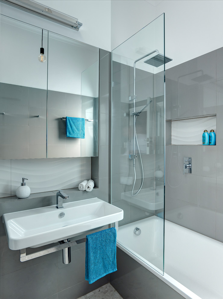 Small contemporary bathroom in Adelaide with an alcove tub, a shower/bathtub combo, gray tile, porcelain tile, marble floors, a wall-mount sink and grey walls.