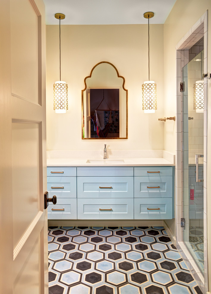 Inspiration for a mid-sized transitional 3/4 white tile alcove shower remodel in Dallas with an undermount sink, shaker cabinets, blue cabinets, quartz countertops and beige walls