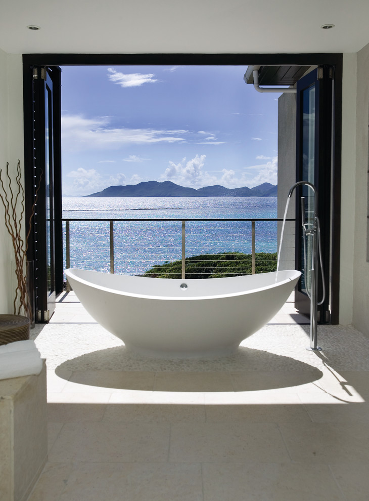 Large island style master beige tile pebble tile floor freestanding bathtub photo in Other with white walls