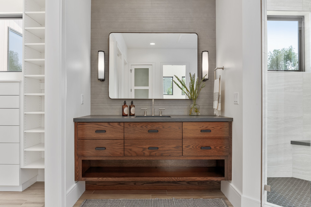 Corner shower - large contemporary master gray tile and porcelain tile porcelain tile and beige floor corner shower idea in Salt Lake City with flat-panel cabinets, medium tone wood cabinets, a one-piece toilet, white walls, an undermount sink, quartzite countertops, a hinged shower door and gray countertops