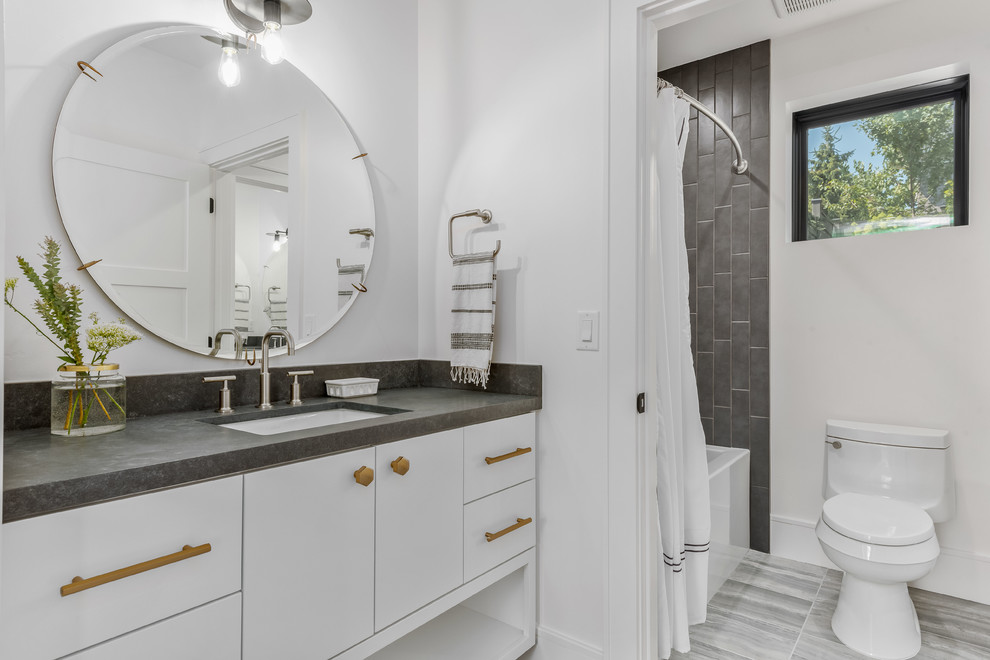Bathroom - large contemporary kids' gray tile porcelain tile and gray floor bathroom idea in Salt Lake City with flat-panel cabinets, white cabinets, a one-piece toilet, white walls, an undermount sink, quartzite countertops and gray countertops