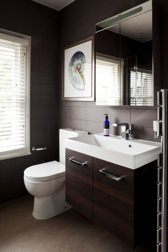 Bathroom - contemporary brown tile bathroom idea in London with a console sink, flat-panel cabinets, dark wood cabinets and a two-piece toilet