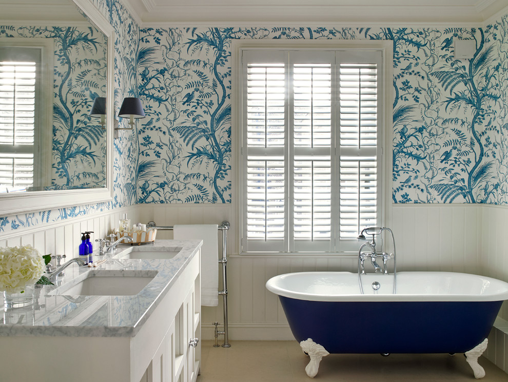 Ornate claw-foot bathtub photo in London with an undermount sink, white cabinets and multicolored walls